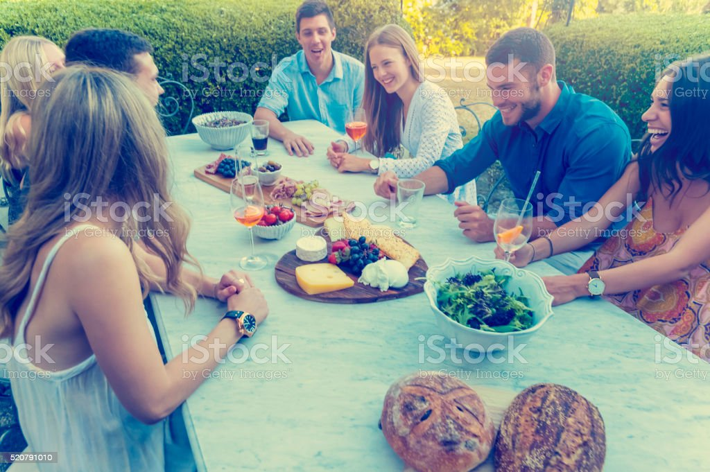 Group of young people eating outdoors. stock photo