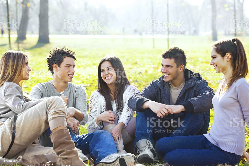 Group of young people enjoying in park on autumn day. royalty-free stock photo