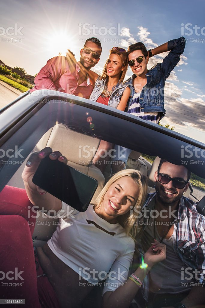 Group of young people enjoying in sunny day in cabriolet. stock photo