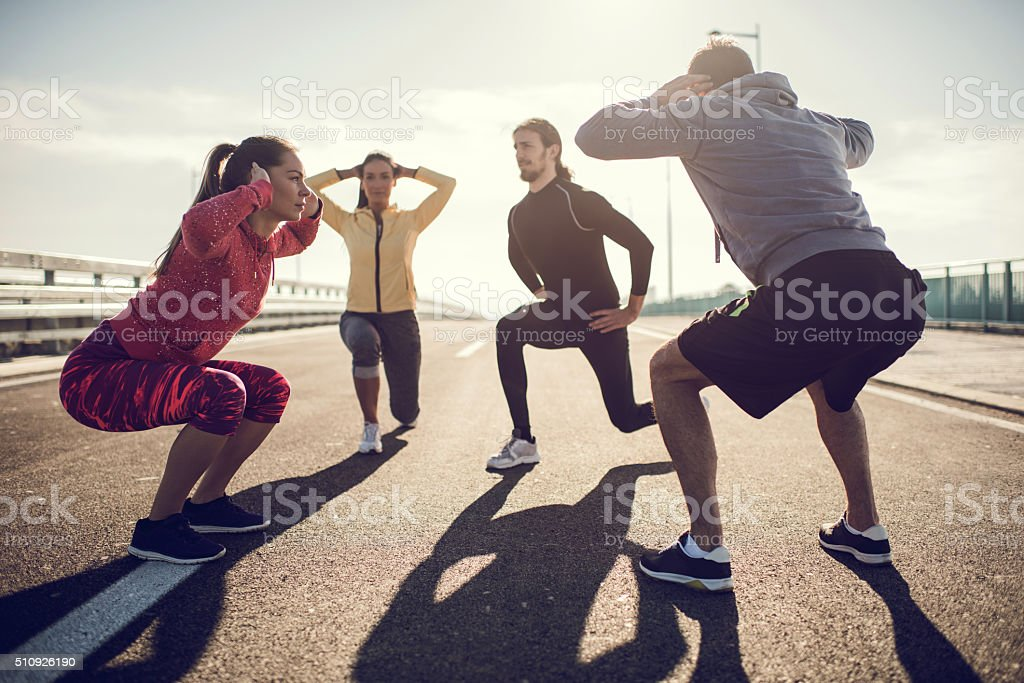 Group of young people exercising on a road. stock photo