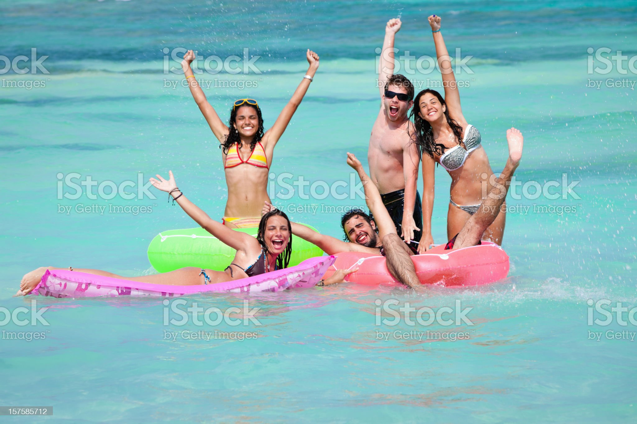 Group of young people floating with tubes in a beach royalty-free stock photo