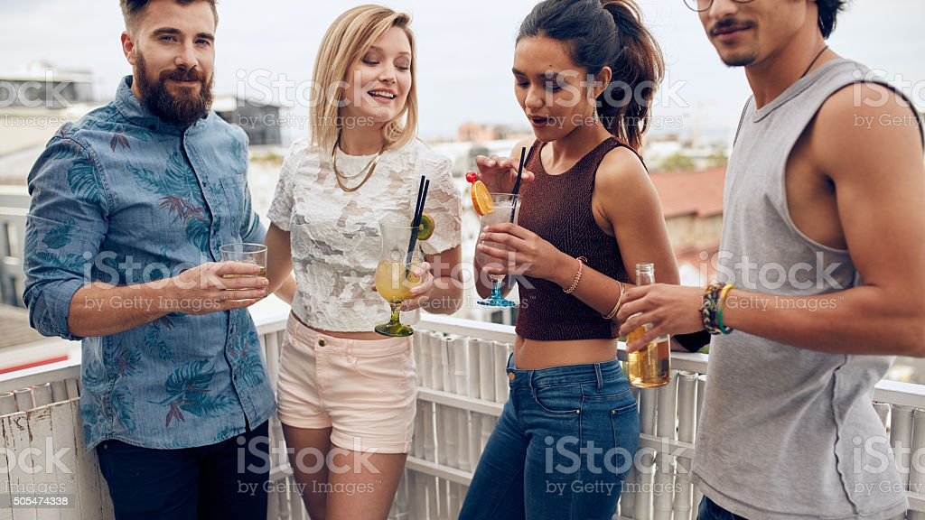 Group of young people having a party on rooftop stock photo
