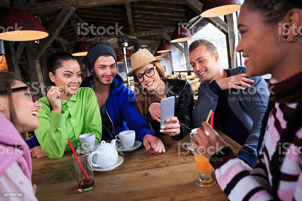 Group of young people having fun in restaurant stock photo