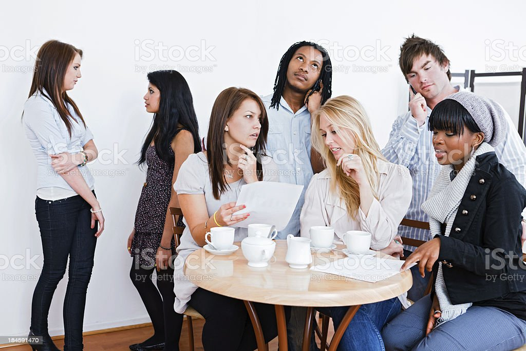 Group of young people in coffeeshop looking concerned by documents royalty-free stock photo