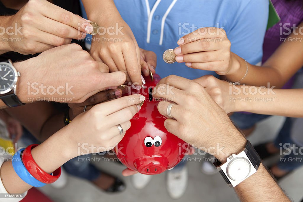 Group of young people inserting coins to a piggy bank. royalty-free stock photo
