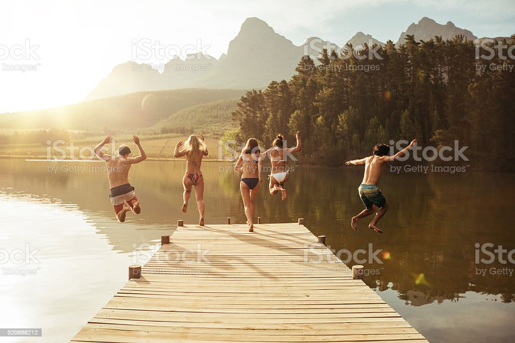 Group of young people jumping into the water stock photo