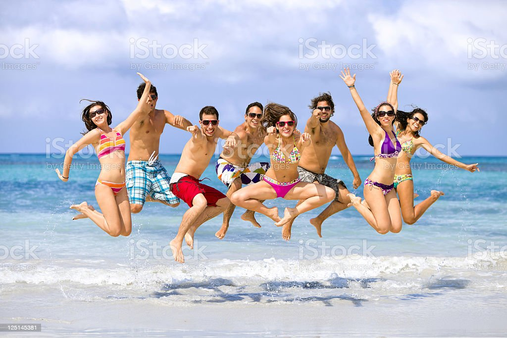 Group of young people jumping on a beach. Spring break. royalty-free stock photo