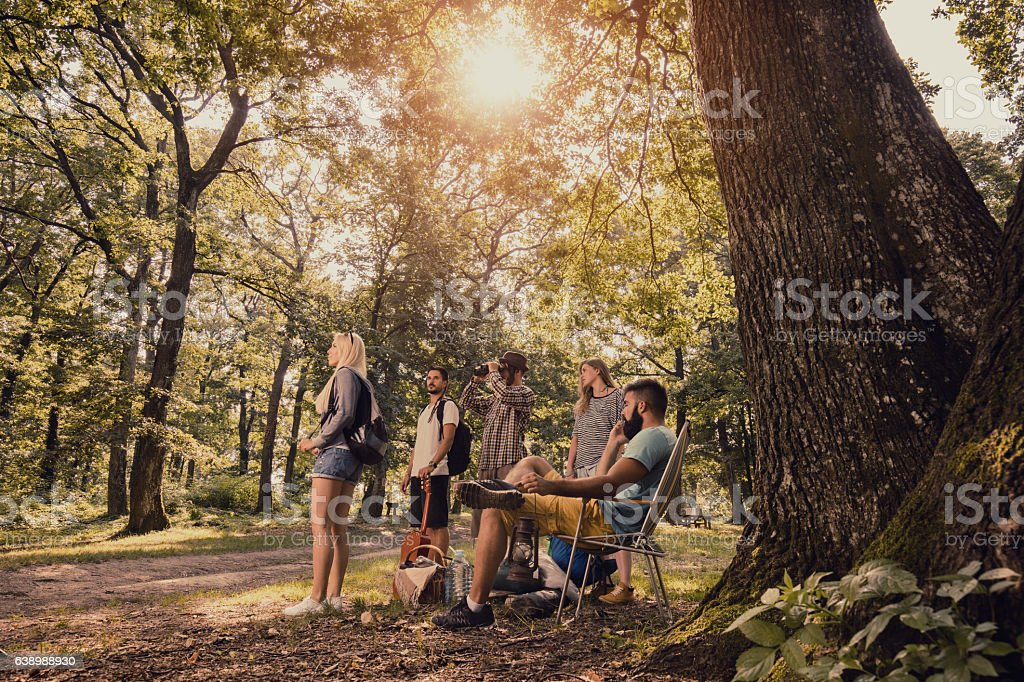 Group of young people looking for place to set camp. stock photo