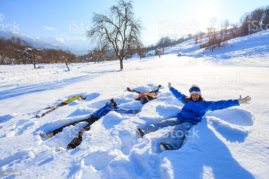 Group of young people making snow angels in the mountain stock photo