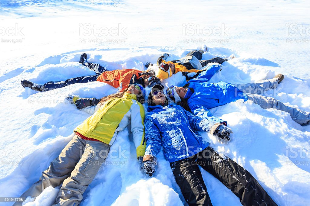 Group of young people making snow angels stock photo