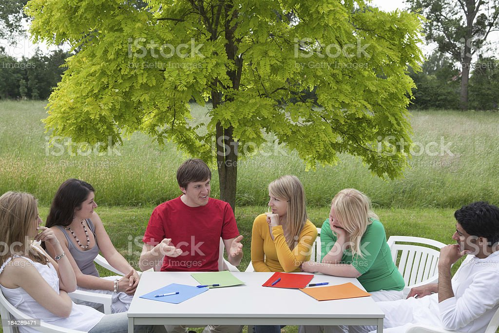 Group of young people outdoors in discussion royalty-free stock photo