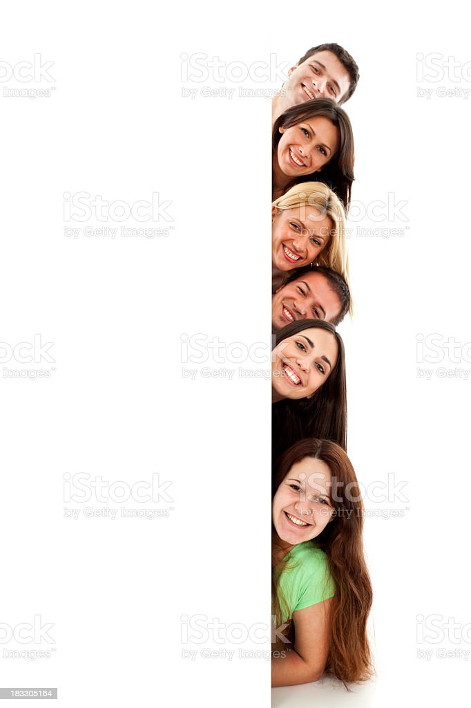Group of young people peeking behind blank banner sign royalty-free stock photo