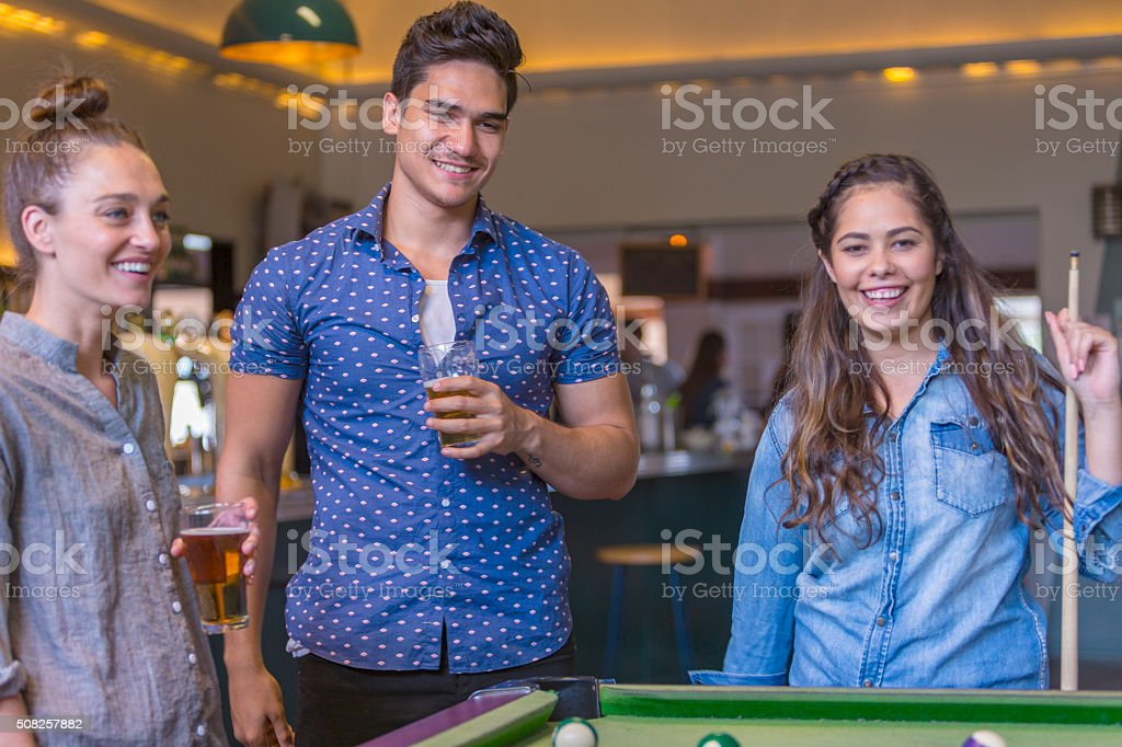 Group of Young People Playing Pool in a Bar stock photo
