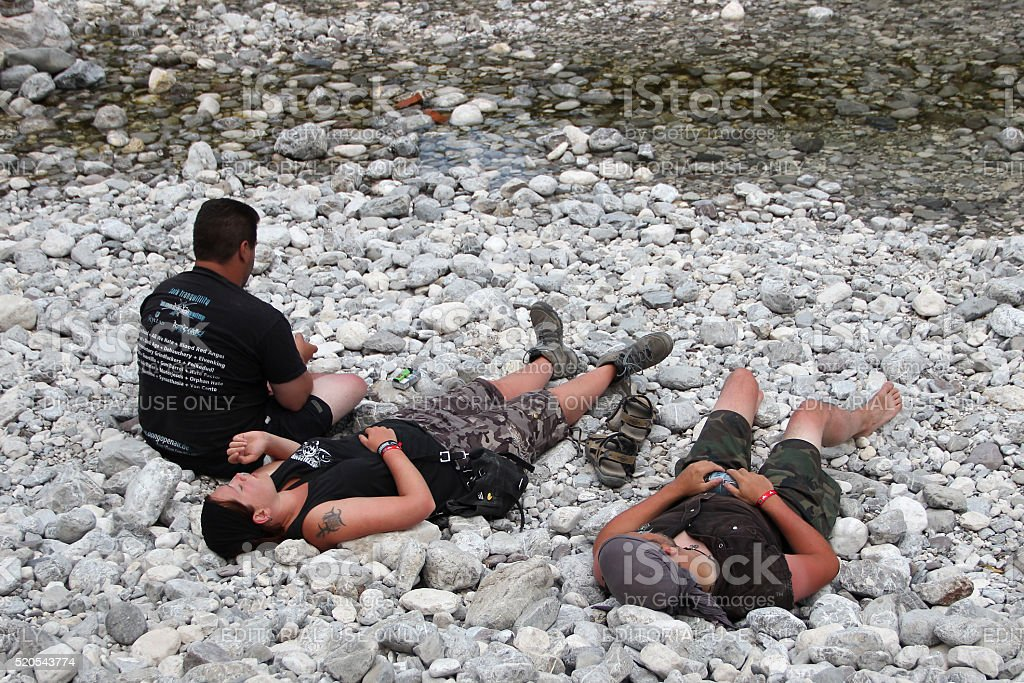 Group of young people resting next to the river. stock photo
