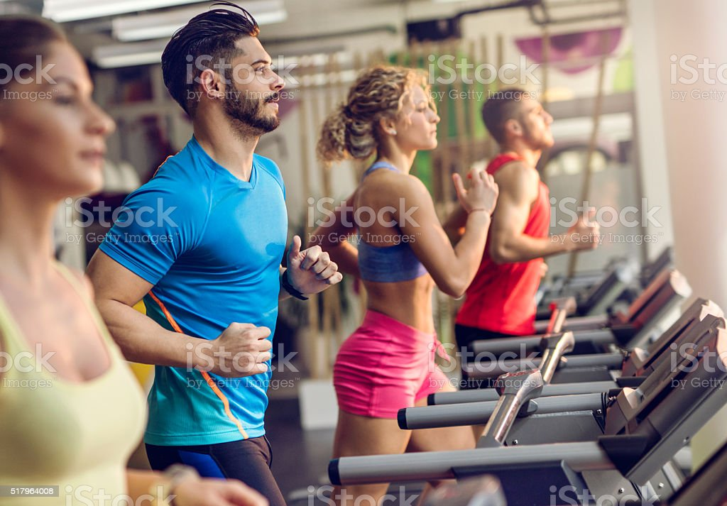 Group of young people running on treadmills in a gym. stock photo