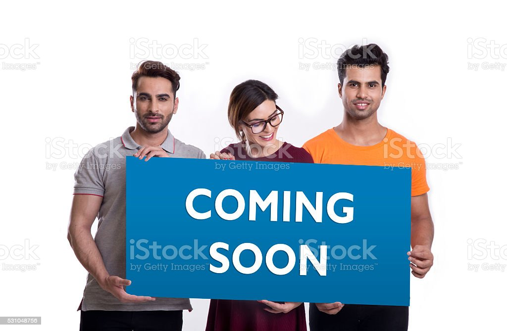Group of young people showing placard of coming soon stock photo