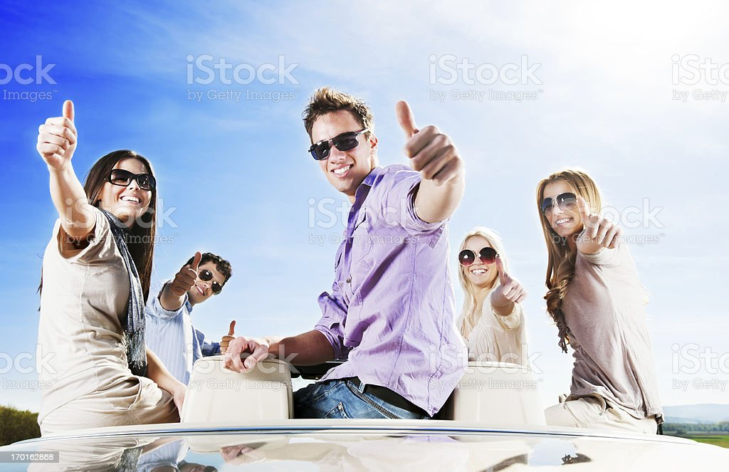 Group of young people sitting on Convertible with thumbs up. royalty-free stock photo