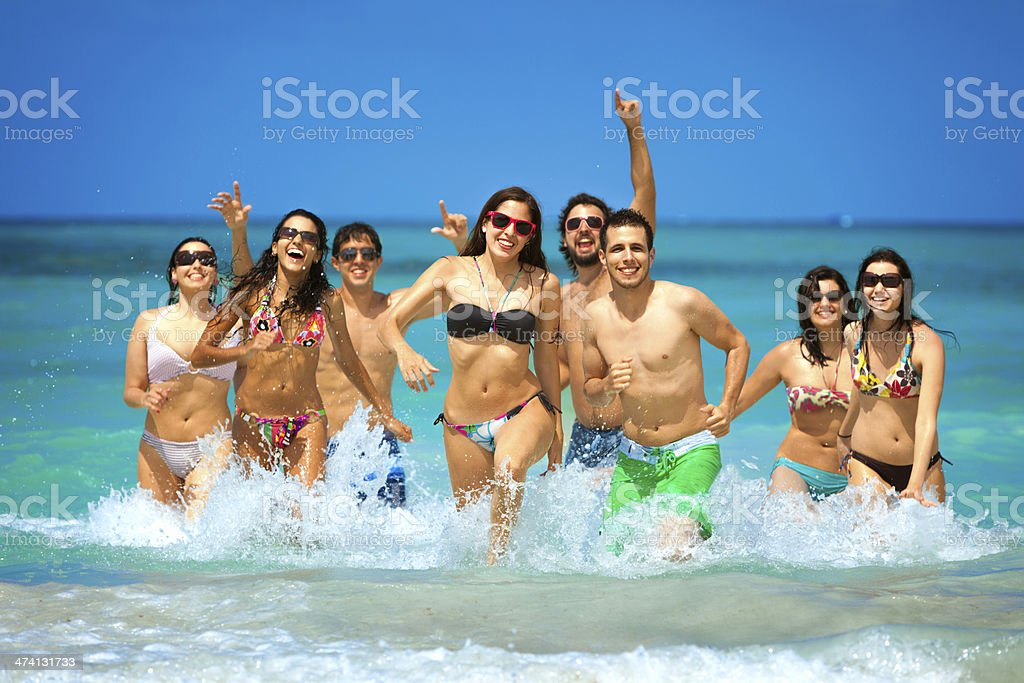 Group of young people splashing in tropical turquoise island beach stock photo