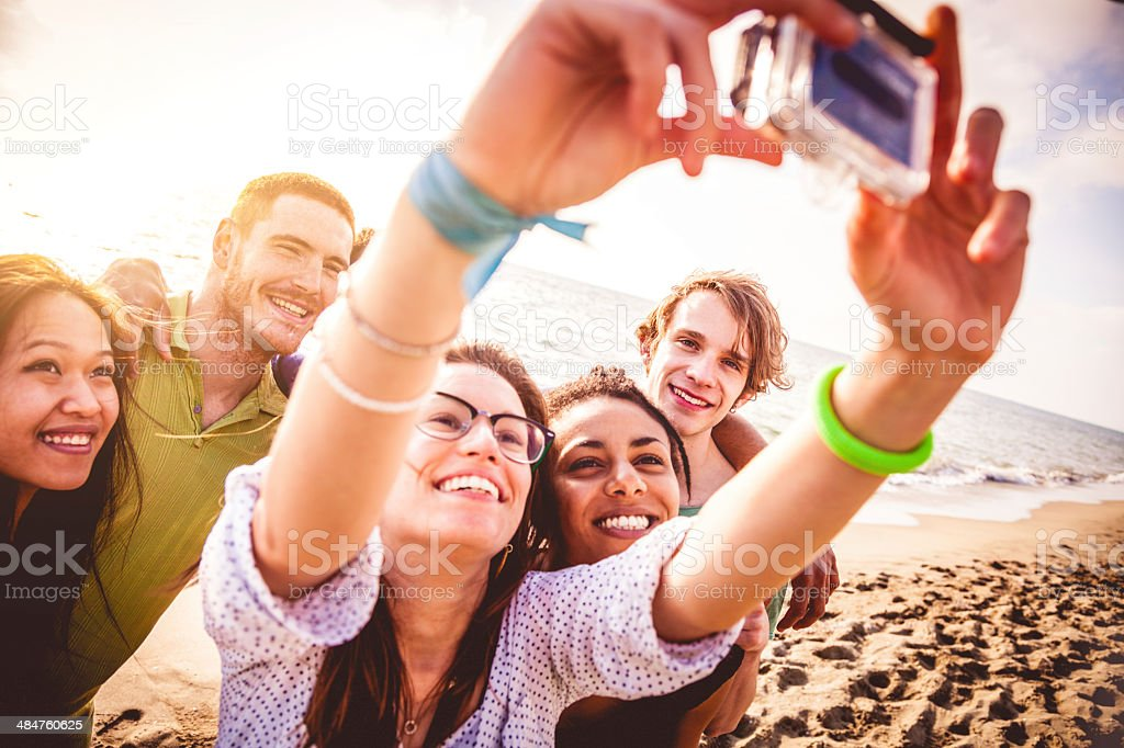 Group of young people take self portrait on beach royalty-free stock photo