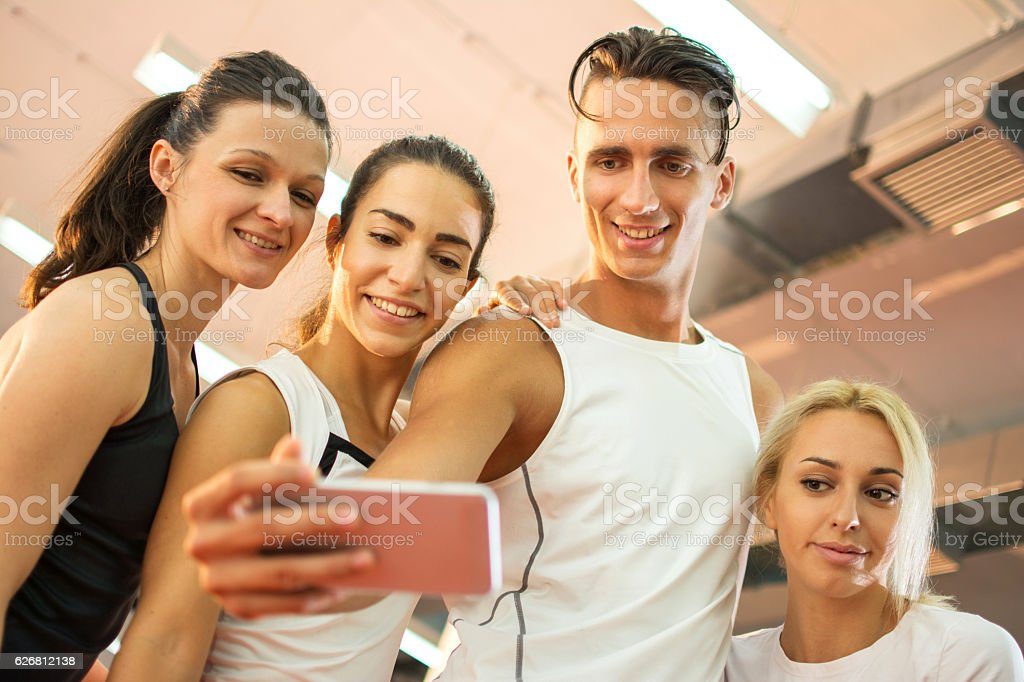 Group of young people taking a selfie in a gym. stock photo