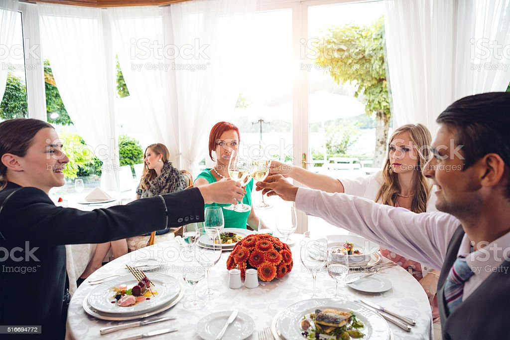 Group Of Young People Toasting At The Dinner stock photo