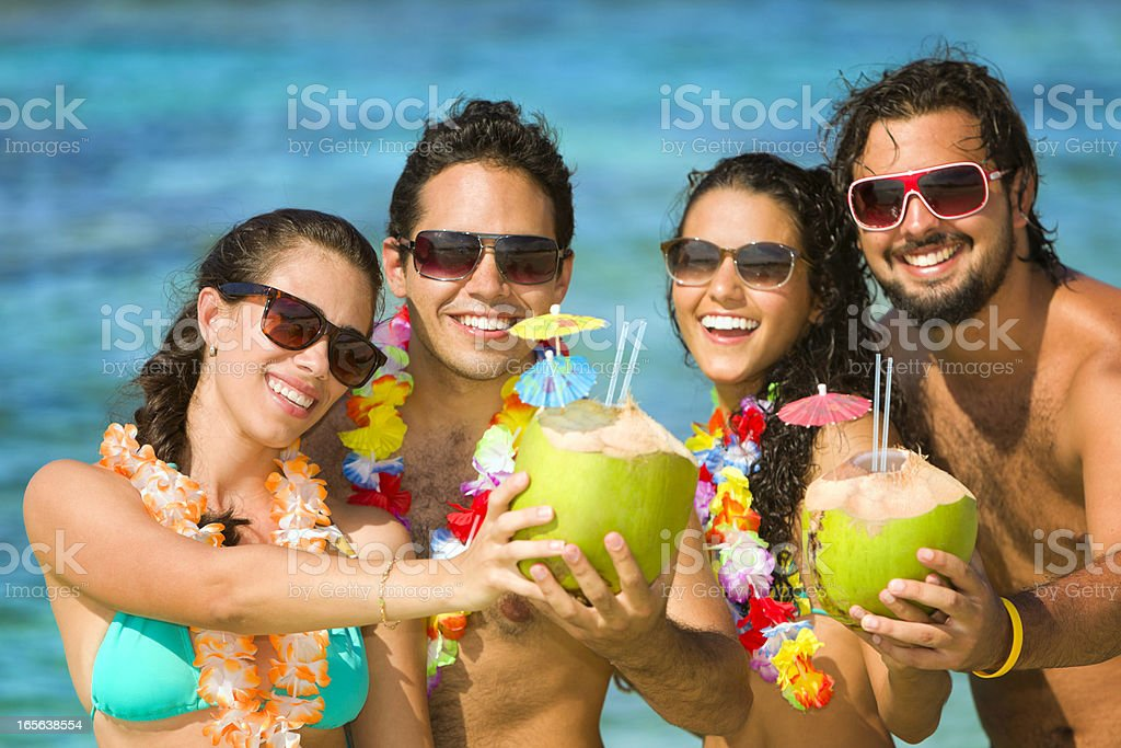 Group of young people toasting in a tropical turquoise beach stock photo
