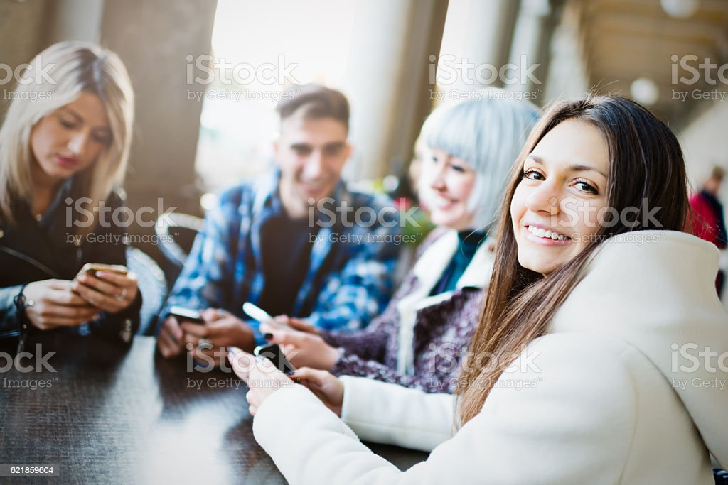 Group of young people using smartphones in sidewalk cafe stock photo
