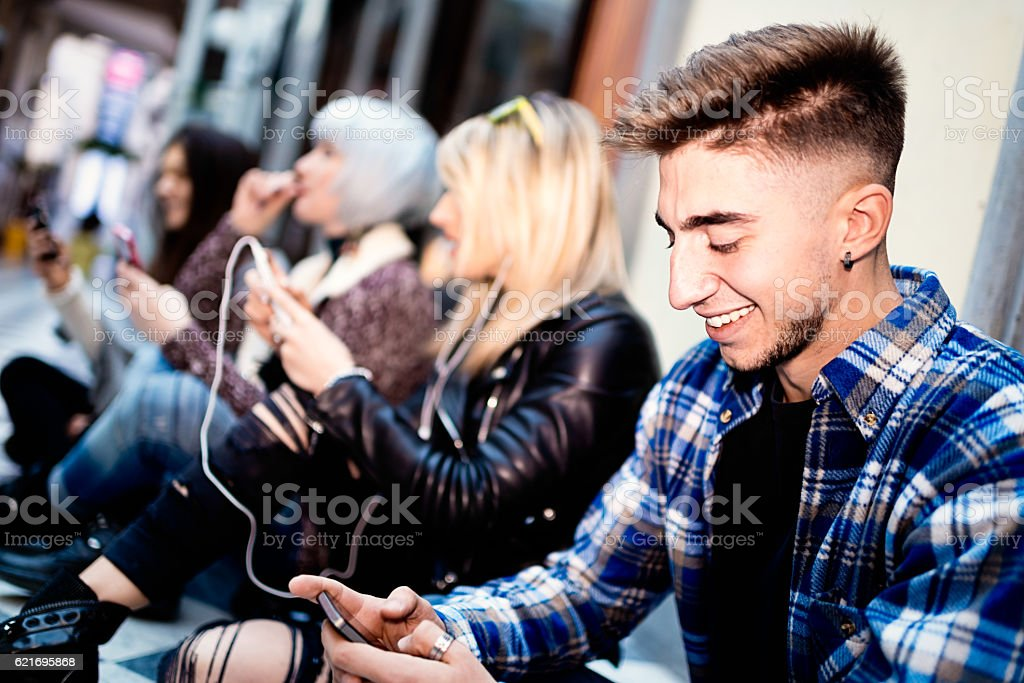 Group of young people using smartphones on street stock photo