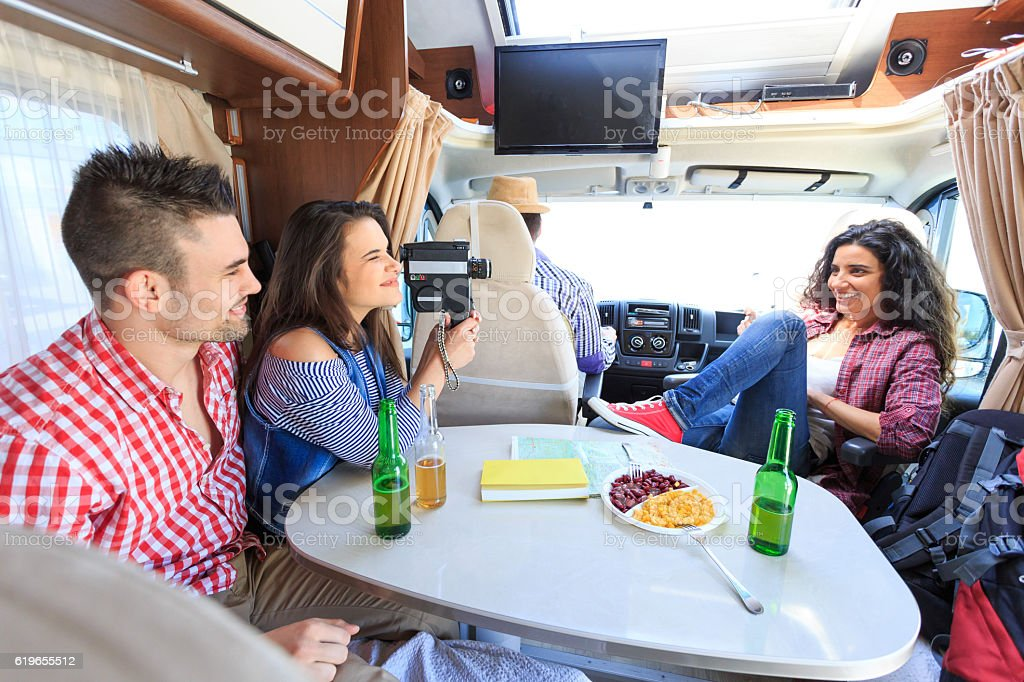 Group of young people using vintage video camera inside camper stock photo