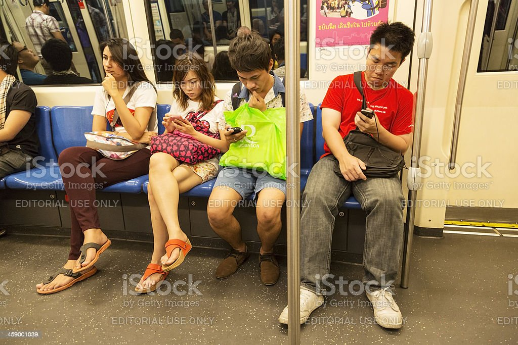 Group of young people with mobiles on MRT, Bangkok metro royalty-free stock photo