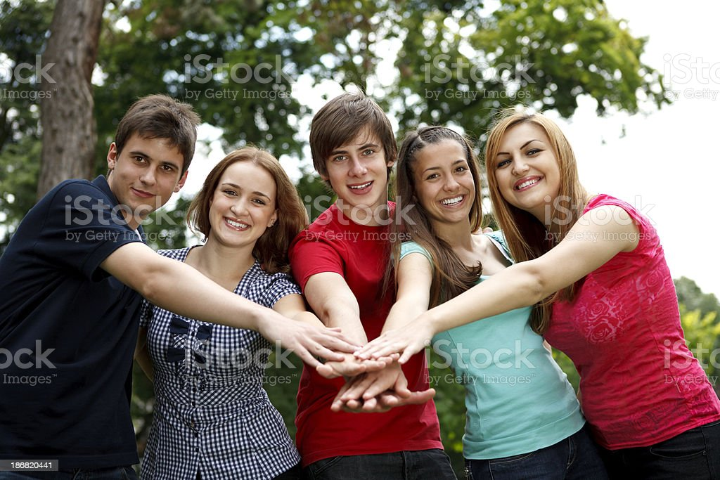 Group of young people with their hands together royalty-free stock photo