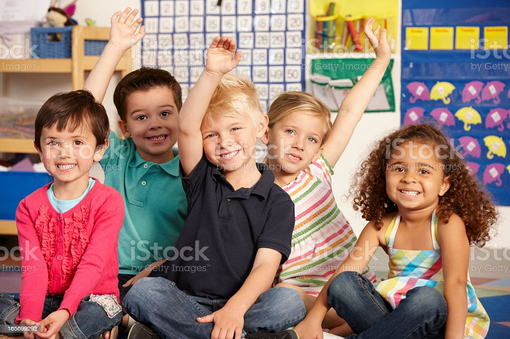 Group of young school kids raising their hands to answer stock photo
