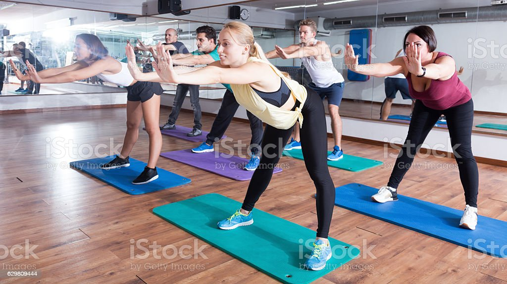 Group of young smiling people studying zumba elements stock photo