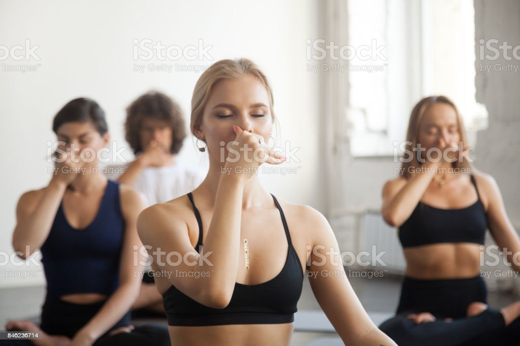 Group of young sporty people making Alternate Nostril Breathing exercise stock photo