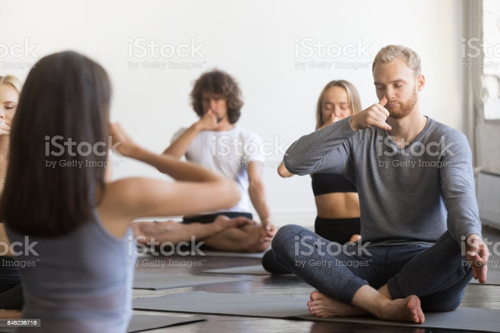 Group of young sporty people making Alternate Nostril Breathing stock photo
