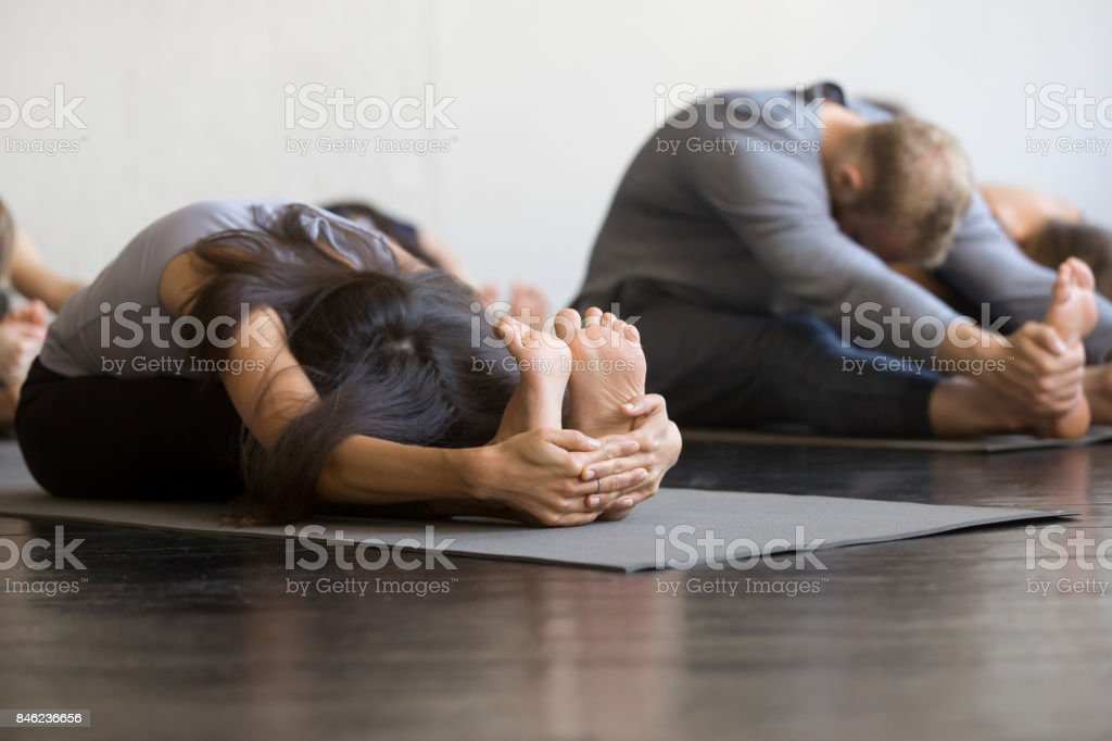 Group of young sporty people Seated forward bend stock photo