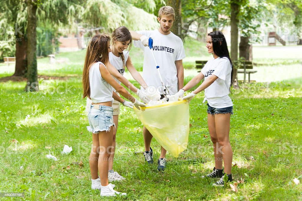 group of young volunteers picking up litter in the park stock photo