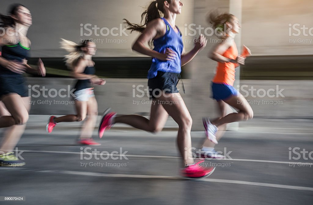 Group of young woman running outdoors stock photo
