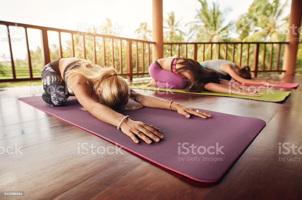 Group of young women doing stretching workout on fitness mat. Women...