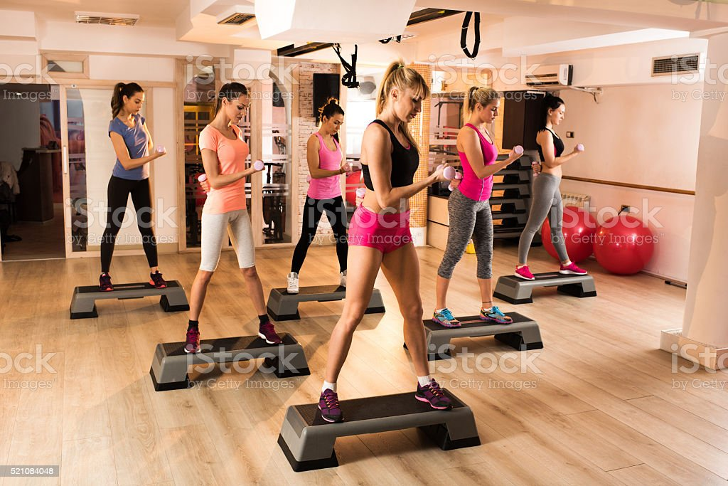 Group of young women exercising step aerobics in a gym. stock photo