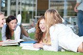 Group of Young Women laying down on grass with books outdoors