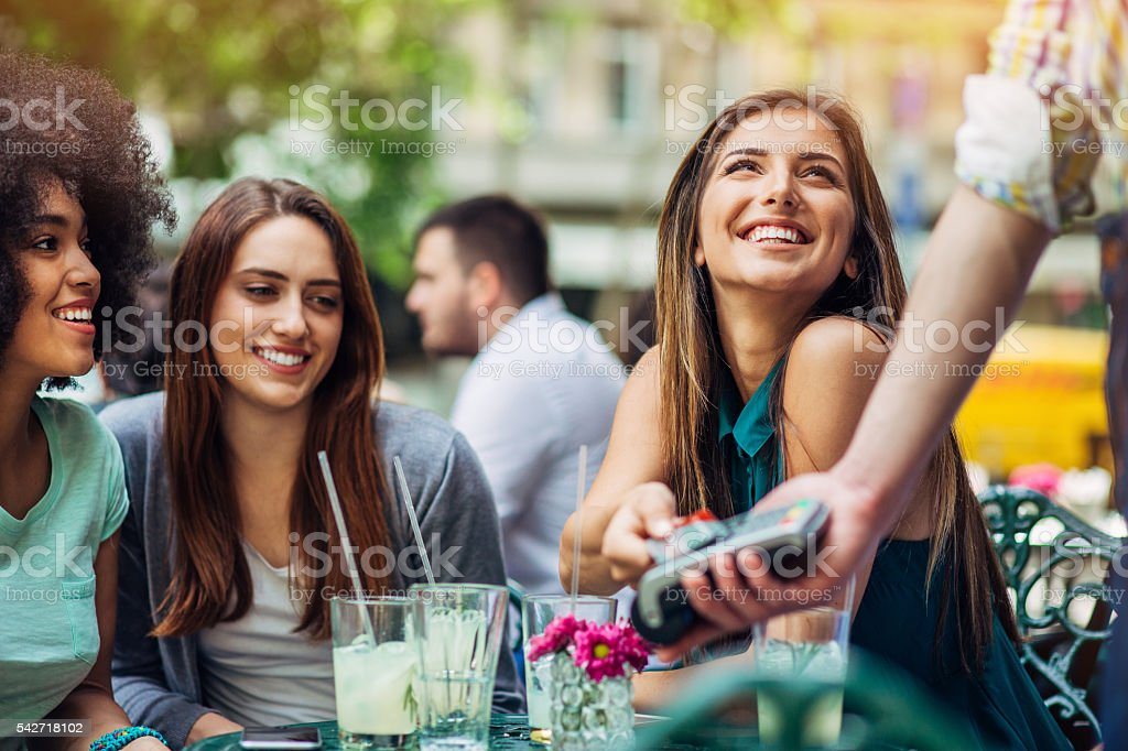 Group of young women paying with credit card in bistro stock photo