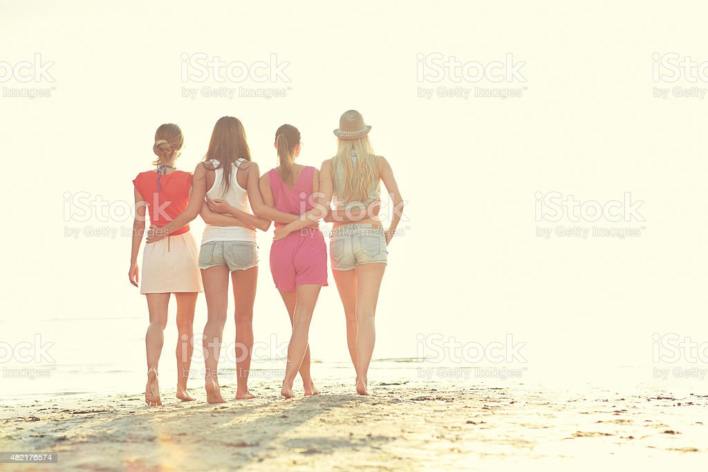 group of young women walking on beach stock photo