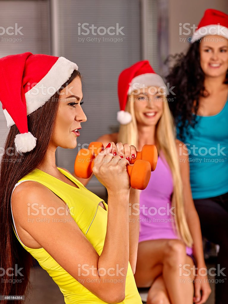 Group people  wearing Santa hat holding dumbbells in sport gym stock photo