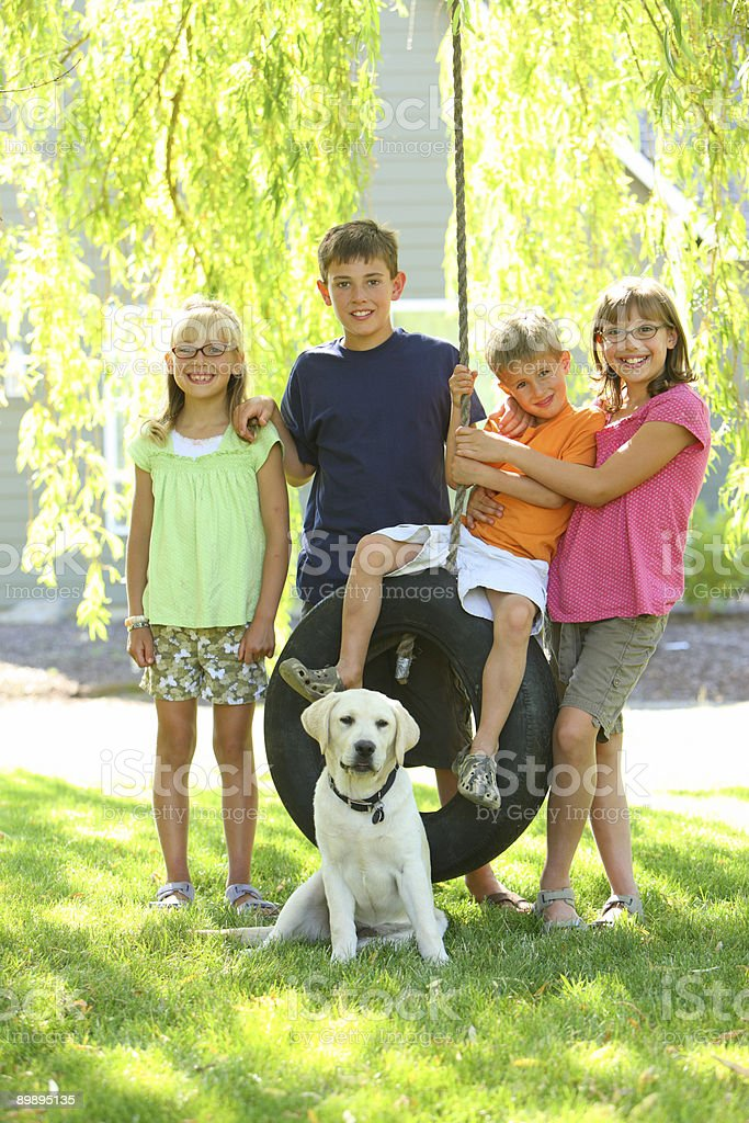 Group portrait of kids and dog by tire swing royalty-free stock photo