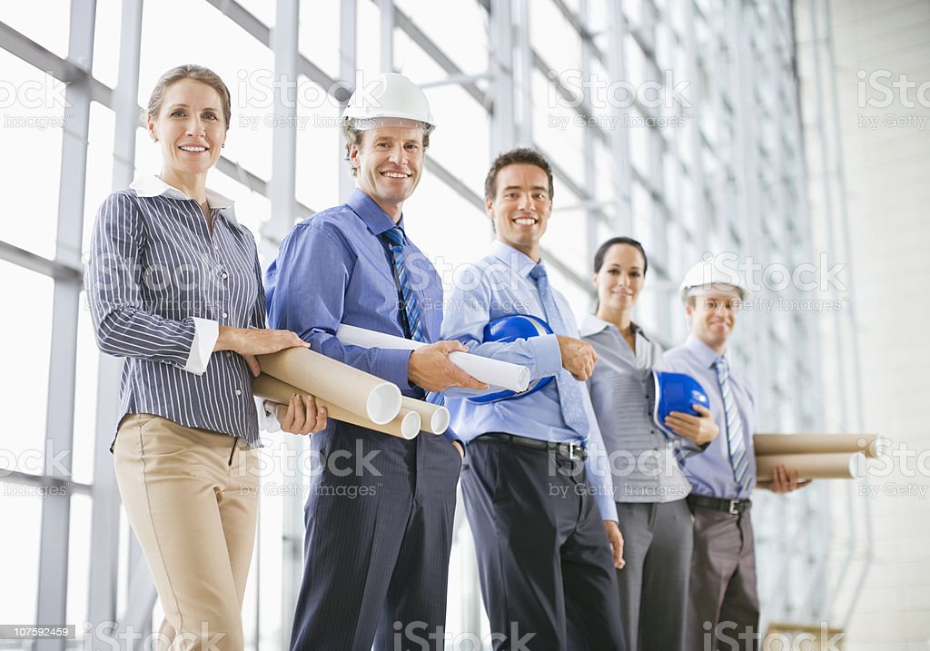 Group portrait of male and female architects with hardhats and blueprints royalty-free stock photo
