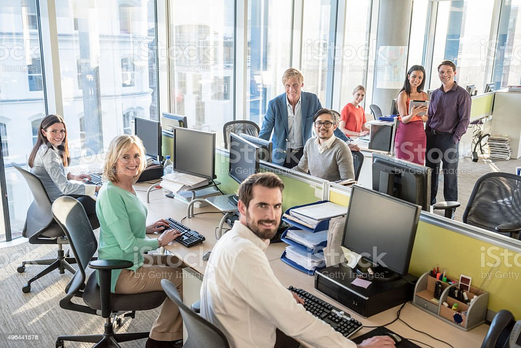 Group portrait of office workers at desks in modern office stock photo