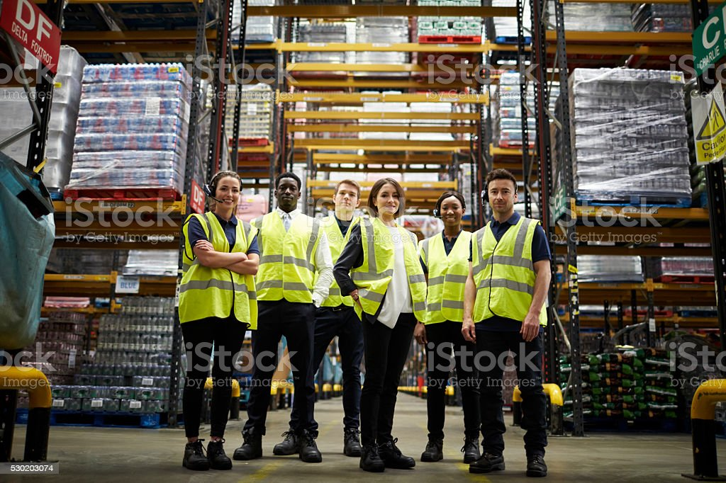 Group portrait of staff at distribution warehouse, low angle stock photo
