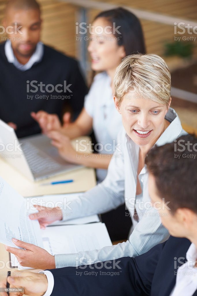 Group sitting at table talking at business meeting royalty-free stock photo