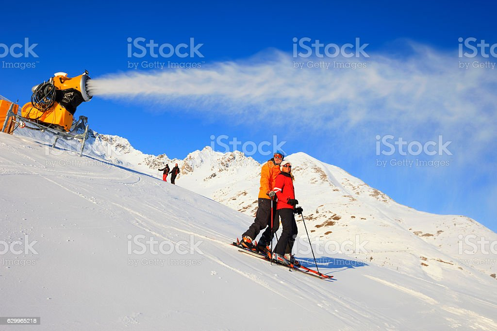 Group skier skiing   Enjoying sunny ski resorts  Snow making machine stock photo